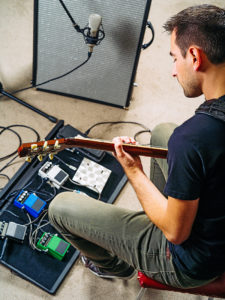 Photo of a man in his late 20's sitting in a rehearsal studio practicing with his electric guitar.