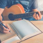 Writing a song with guitar pen and paper